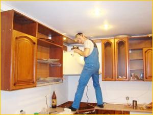 Мастер ремонтирует кухонный гарнитур