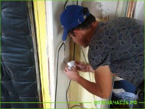 Электрик производит замену выключателя в коридоре