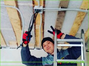 Электрик прокладывает проводку на потолке в частном доме