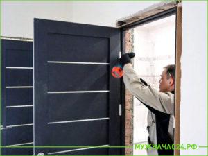 Установщик устанавливает черную межкомнатную дверь
