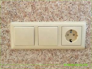 Два выключателя и одна розетка бежевого цвета в кухоном фартуке